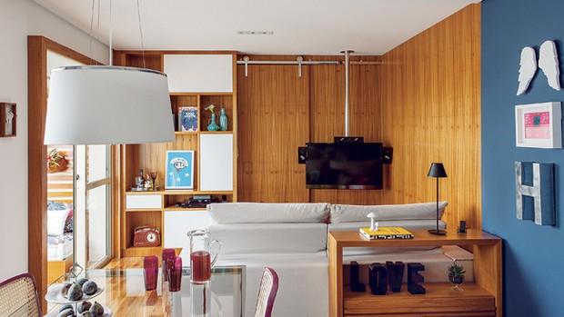 Feito pela Móveis Nello, o painel de freijó delimita as salas de estar e jantar. A TV está presa ao teto pelo suporte da Keyato Ferragens. Com 36 cm de profundidade, o armário tem nichos que se abrem com o toque da mão. Vasos da L'Oeil. Quadro do artista  (Foto: Edu Castello)