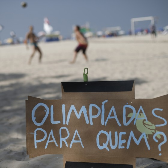 Placa de protesto contra a Olimpíada na Praia de Copacabana, no Rio (Foto: Silvia Izquierdo/AP)
