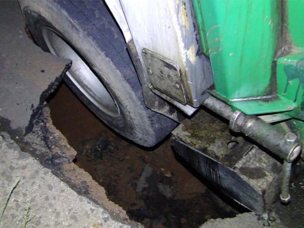 Roda traseira ficou presa em cratera na rua (Foto: Helder Almeida / Clic Folha)