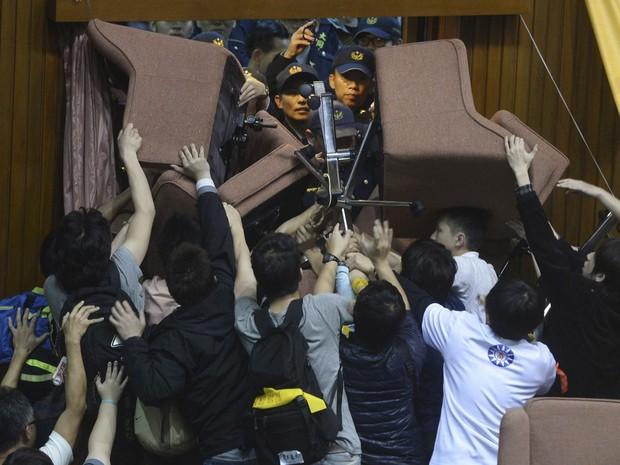 Estudantes taiwaneses que invadiram o parlamento em Taipei bloqueiam uma porta amontoando cadeiras para barrar a entrada da polícia. Os manifestantes invadiram o local para impedir a votação de um pacto de comércio com a China sem revisão item a item (Foto: AP)