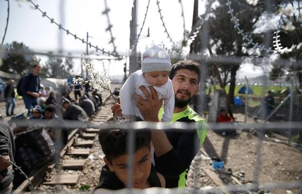 Imigrante mostra bebê enquanto aguarda ao lado de cerca na fronteira da Grécia com a Macedônia (Foto: Marko Djurica/Reuters)
