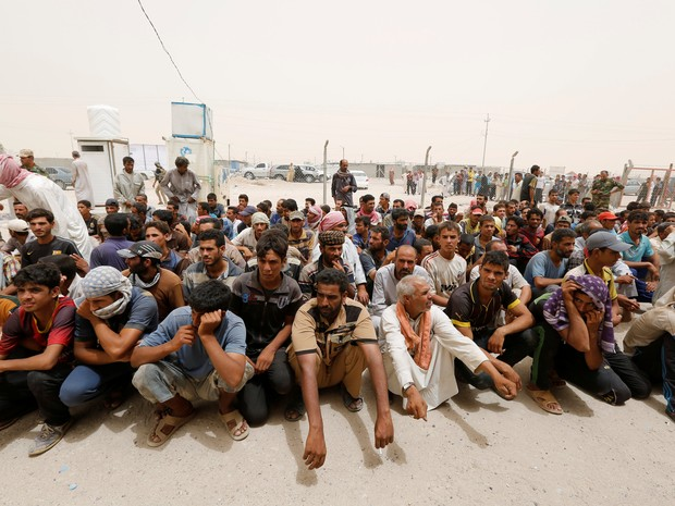 Deslocados internos esperam o controle de segurança de combatentes tribais durante tempestade de areia no campo ao sul de Faluja, no Iraque; país é o segundo em número de deslocados internos, segundo relatório da ONU divulgado nesta segunda-feira (20) (Foto: REUTERS/Ahmed Saad)