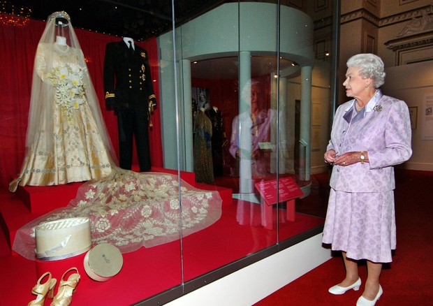 EMBARGOED UNTIL 0600 FRIDAY JULY 27, 2007  Britain's Queen Elizabeth II shown on 24/07/2007 looking at her 1947 wedding gown and 13-foot bridal trail designed by Norman Hartnell with the naval uniform worn by the Duke of Edinburgh, which are on show for t (Foto: PA Archive/PA Images)