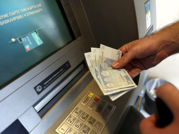 Um homem saca 60 euros, o limite máximo diário, em um caixa eletrônico em Piraeus, perto de Atenas, na Grécia. Nesta terça (30) termina o prazo para que o país pague uma parcela de 1,6 bilhão de euros ao FMI e continue na Zona do euro (Foto: Yannis Behrakis/Reuters)
