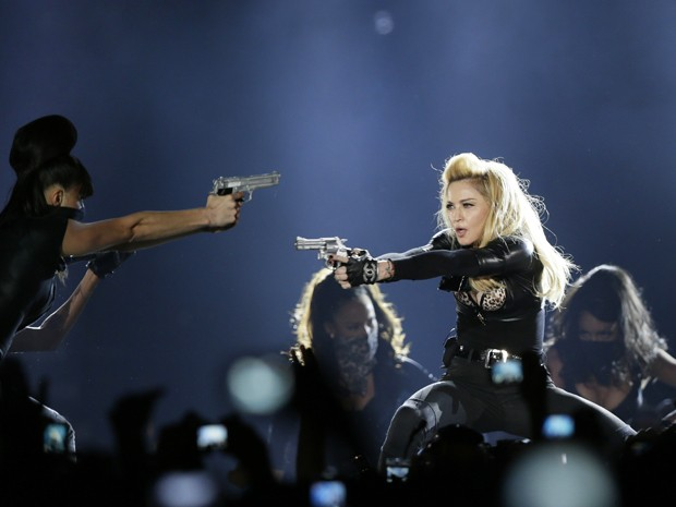 Madonna aponta arma durante encenação em show no Stade de France, em Paris, neste sábado (14) (Foto: Kenzo Tribouillard/AFP)