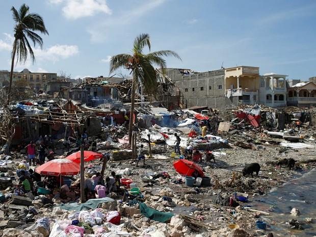 Pessoas se reúnem à beira-mar em local atingido pelo furacão Matthew em Jeremie, no Haiti (Foto: Carlos Garcia Rawlins/Reuters)