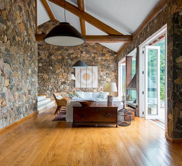 Sala de estar | Os troncos de eucalipto com stain Polisten, da Sayerlack, sustentam o telhado; o forro é de lambris de madeira com esmalte sintético. Assoalho de réguas de ipê de demolição. Quadro de mandala adquirido em viagem ao Oriente (Foto: Edson Ferreira/Divulgação)