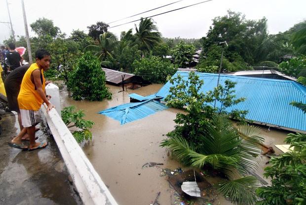 Moradores olham os estragos causados por tempestade em Misamis Oriental, no sul da ilha filipina de Mindanao, nesta segunda-feira (29) (Foto: Erwin Mascarinas/AFP)