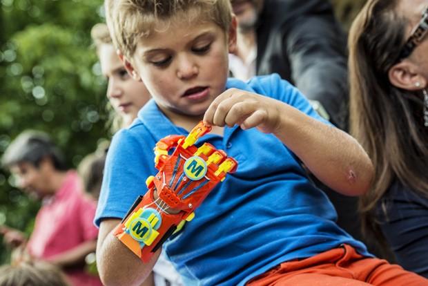 Garoto que nasceu com malformação na mão direita observa sua nova prótese feita com impressora 3D  (Foto: AFP Photo/Jeff Pachoud)