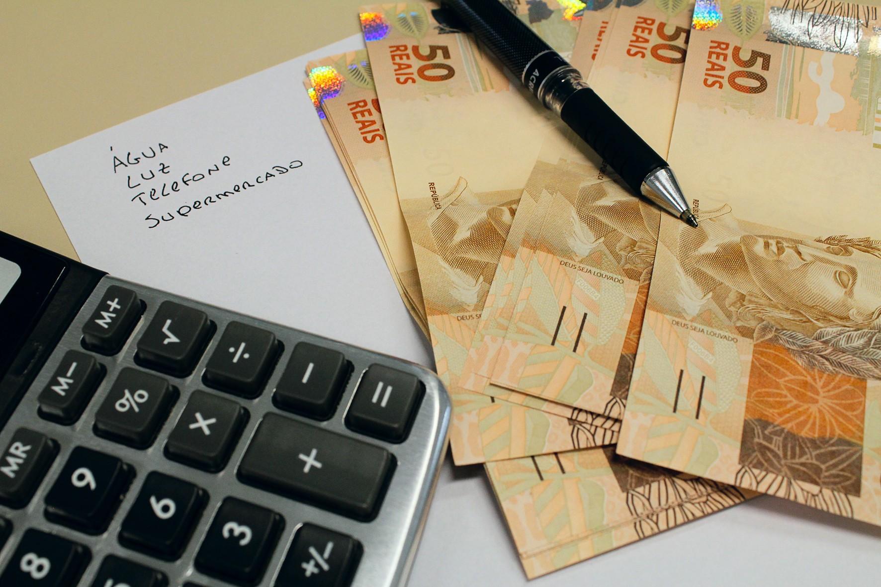 Cédulas de real e uma calculadora ao lado de contas. notas, dinheiro, reais, cotação, câmbio, valor, economia, crise, pobreza. -HN-