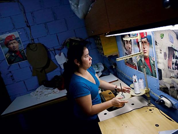 2. Maria trabalha como costureira diante  de imagens de  do libertador  Simón Bolívar e  do presidente Hugo Chávez (Foto: Jorge Silva)