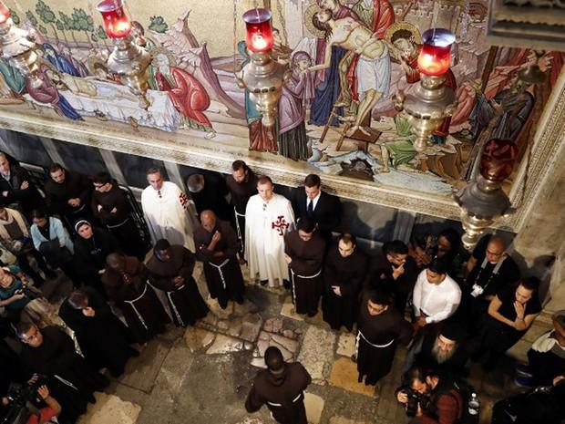 Padres franciscanos participam de cerimônia na igreja do Santo Sepulcro, em Jerusalém, nesta sexta-feira (25) (Foto: Thomas Coex / AFP)