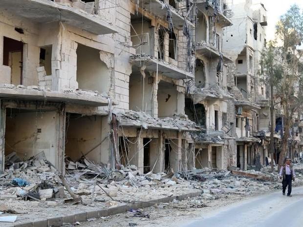 Homem caminha ao lado de prédios destruídos no bairro controlado por rebeldes al-Sukkari em Aleppo, na Síria (Foto: Abdalrhman Ismail/Reuters)