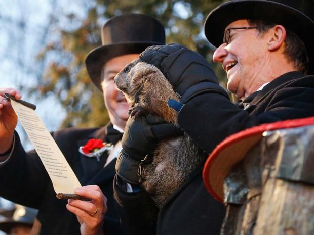 Treinador John Griffiths lê 'previsão' da marmota Phil nesta terça-feira (2) após o bicho prever primavera antecipada nos Estados Unidos (Foto: AP Photo/Keith Srakocic)