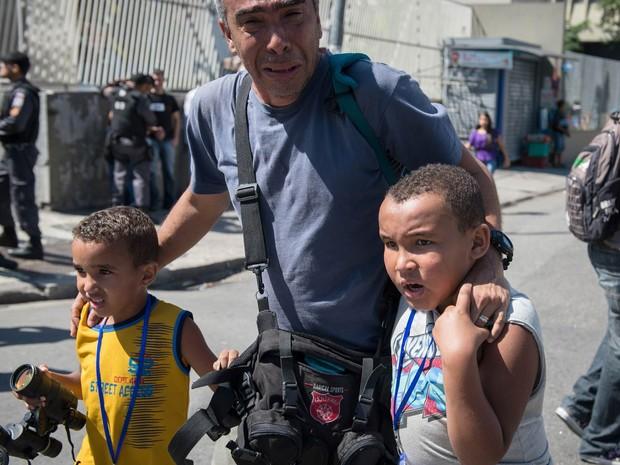 Homem leva seus filhos em meio á confusão durante confronto entre manifestantes e a polícia no desfile do Rio de Janeiro. (Foto: Yasuyoshi Chiba/AFP)