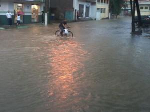 Ciclista se arrisca para atravessar a rua alagada em Maruípe, Vitória.  (Foto: Marcelo Pinheiro/ VC no G1)