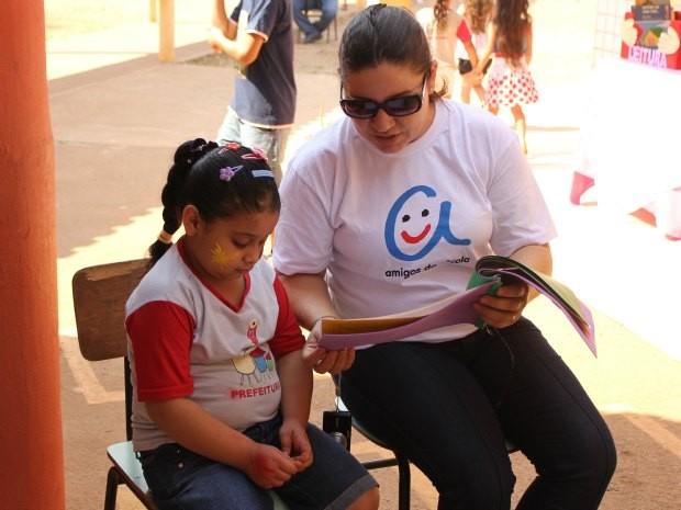 Colaboradora lê para criança no dia temático (Foto: Jenifer Zambiazzi/G1)