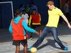 Com camisa do Brasil, Príncipe Harry joga bola com crianças carentes