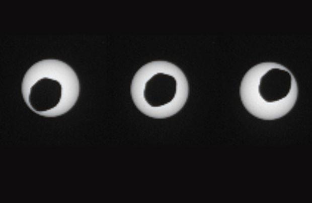 Sequência de três fotos com três segundos de diferença mostram Phobos passando diante do Sol. (Foto: AFP/Nasa)