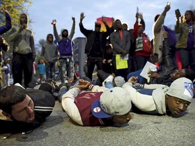 Manifestantes fingem ser presos em frente à delegacia de polícia de Baltimore. (Foto: Sait Serkan Gurbuz / TPX / Via Reuters)