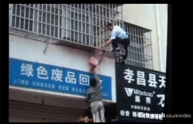 Menina de 4 anos é socorrida após ficar pendurada da janela do 4º andar de prédio na China (Foto: Reprodução)