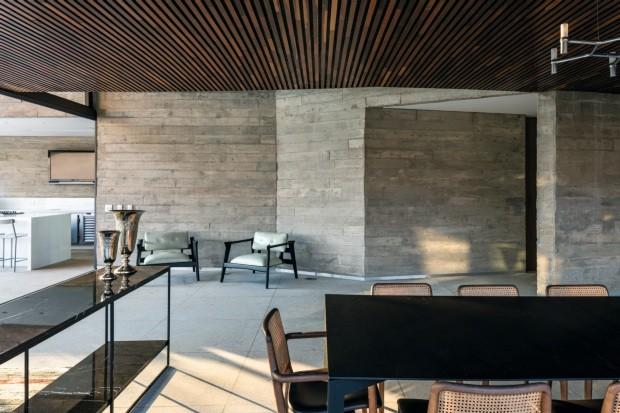 Sala de jantar. Com a parede de concreto (ao fundo) isolando a cozinha, o espaço tem mesa da TomSobre Tome cadeiras da Axis Móveis. Pendente da La Lampe. Aparador e poltronas da Sava Móveis (Foto: Leonardo Finotti e Daniel Mansur / Divulgação)