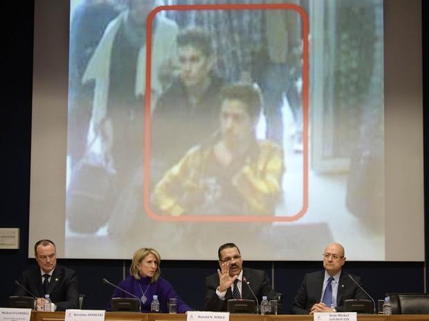 11/3 - O secretário-geral da Interpol, Ronald Kenneth Noble (2º da direita) fala à imprensa ao lado de outros oficiais enquanto é exibida a foto dos dois suspeitos no desaparecimento do voo MH370, em Lyon, no sul da França (Foto: Philippe Desmazes/AFP)