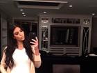 De vestido justinho, Kim Kardashian posa com a mão na barriga