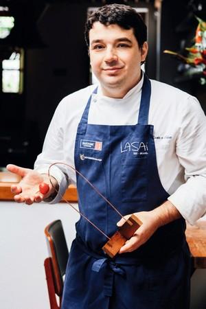 O chef Rafael Costa e Silva, com a armação de cobre e o rabanete que compõem o arranjo de cada mesa (Foto: Ângelo dal Bó / Editora Globo)