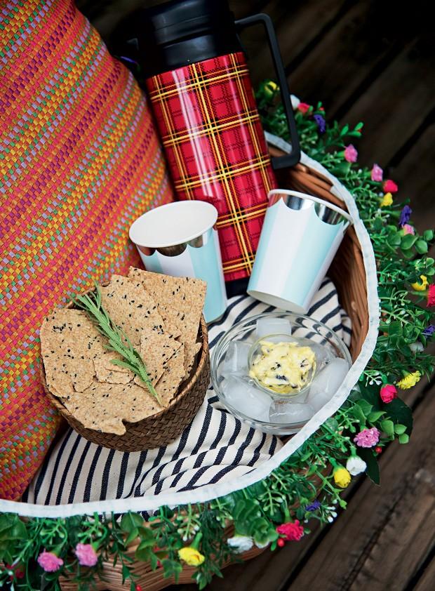 O festão de flores – comprado em lojas de artigos de festa - é um amigo camarada na hora do piquenique. A cestinha que acomoda as bebidinhas e os quitutes pode ser decorada para combinar com o clima ao ar livre. (Foto: Cacá Bratke/Casa e Comida)
