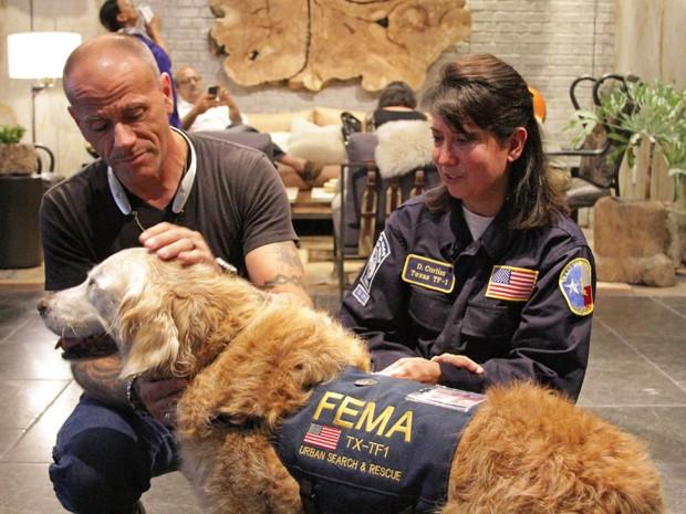 Christopher Wilson brinca com Bretagne, ao lado de sua dona, Denise Corliss, durante as comemorações do 16º aniversário da cachorra, que atuou na busca de vítimas do 11 de Setembro, em foto de 22 de agosto (Foto: Wheaton Simis/BarkPost.com via AP)