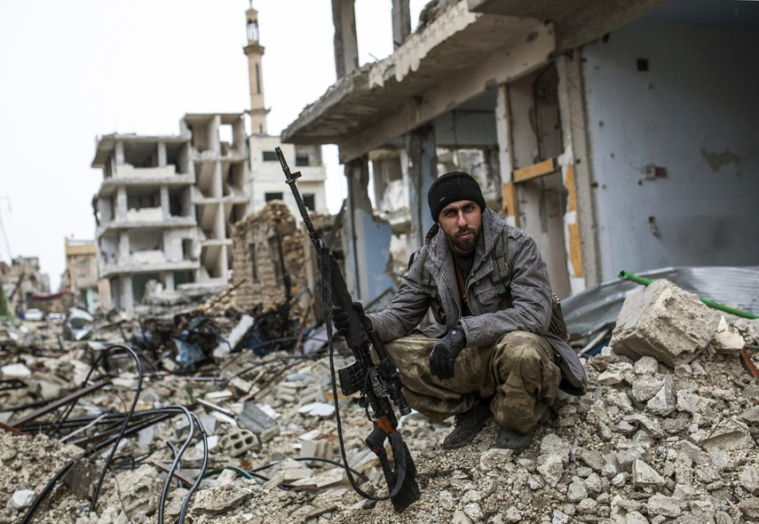 In this picture taken Friday, Jan. 30, 2015, a Syrian Kurdish sniper sits among the rubble in the Syrian city of Ain al-Arab, also known as Kobani, Syria. The Islamic State group has acknowledged for the first time that its fighters have been defeated in