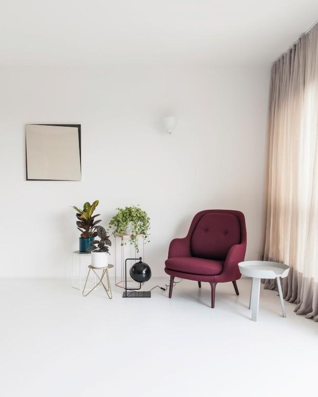 Canto da sala de estar. A poltrona da Atec Original Design, em tom vinho, reina cercada por suportes de plantas da Selvvva (Foto: Maíra Acayaba / Editora Globo)