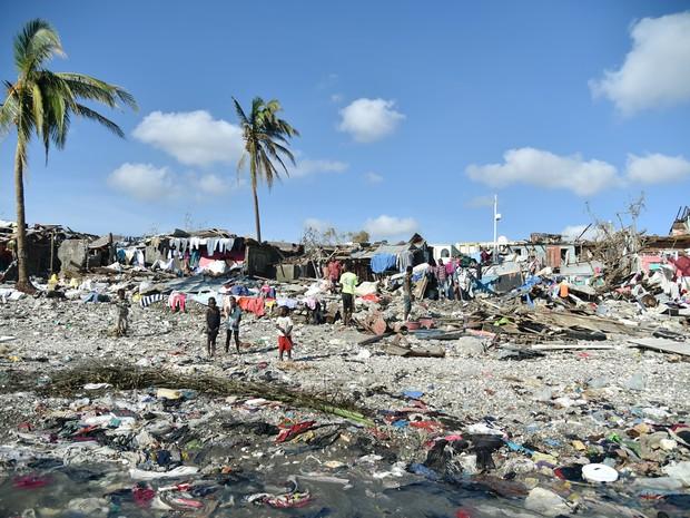 Pessoas caminham em frente a casas destruídas pelo furacão Matthew em Jeremie, no Haiti. (Foto: Hector Retamal/AFP)