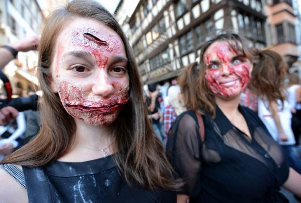 Menina com a boca costurada participa da marcha dos zumbis realizada em cidade da França. (Foto: Patrick Hertzog/AFP)