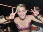 De top e saia curtinha, Miley Cyrus se diverte em festa