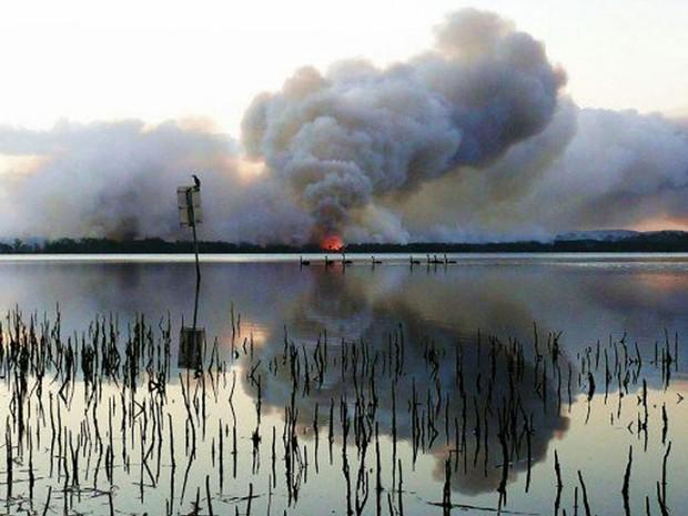 Acelerado pelas altas temperaturas e ventos na região, incêndio toma conta de área rural perto do Green Point no estado australiano de New South Wales. O fogo colocou moradias em risco e motivou a retirada de moradores. (Foto: AFP/NSW Rural Fire Service)