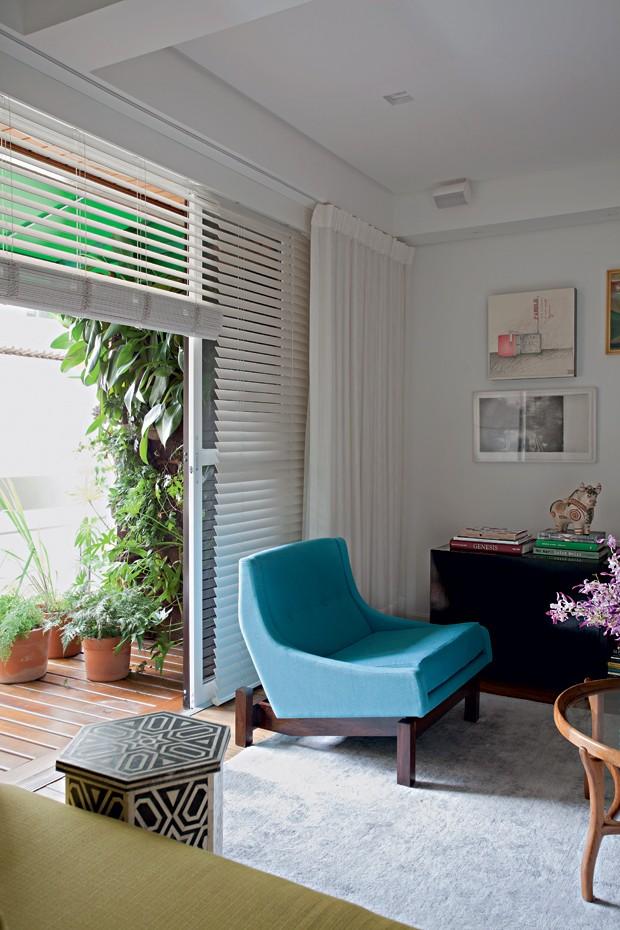 Varanda | O azul da poltrona Paraty, de Sergio Rodrigues, oferece frescor à sala, assim como a luz que vem da varanda, com paisagismo de Alessandro Terracini (Foto: Marco Antonio/Casa e Jardim)