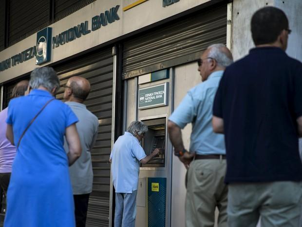 Pessoas fazem fila para sacar dinheiro neste domingo, em Atenas (Foto: REUTERS/Marko Djurica)