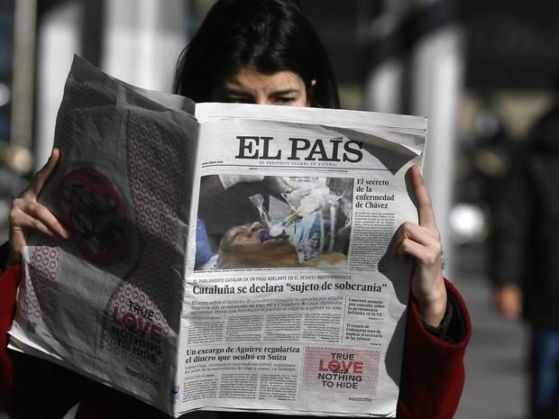 Mulher lê edição do jornal espanhol 'El País' com foto que mostra um homem entubado que uma agência de notícias havia fornecido à publicação afirmando que se tratava de Hugo Chávez. O jornal decidiu paralisar a distribuição ao constatar o erro. (Foto: Andrea Comas/Reuters)