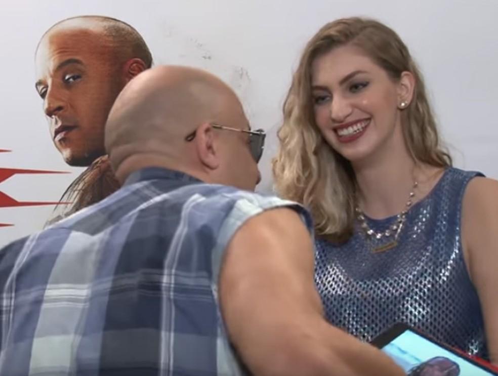 Vin Diesel se ajoelha diante de Carol Moreira durante entrevista em São Paulo (Foto: Reprodução/YouTube/Carol Moreira)