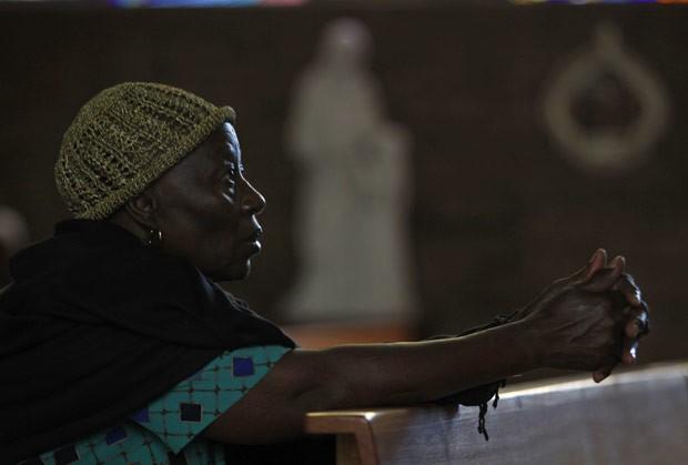 Sul-africana ora em intenção do ex-presidente Nelson Mandela nesta terça-feira (11) em Soweto (Foto: AP)