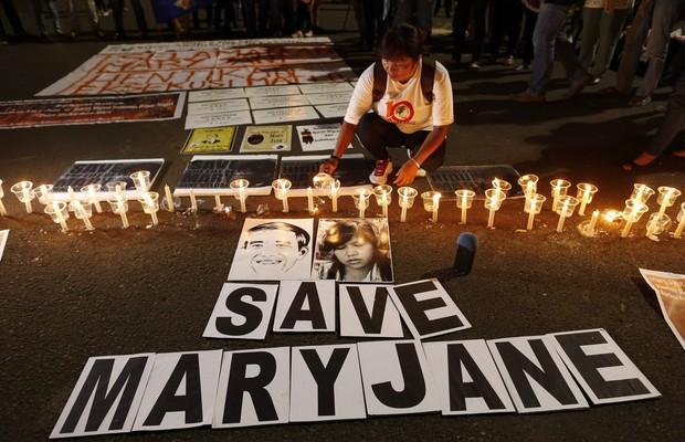 Imigrantes que trabalham na Indonésia acendem velas em homenagem a Mary Jane Veloso, das Filipinas. Ela foi condenada a morte por tráfico de drogas (Foto: EFE)