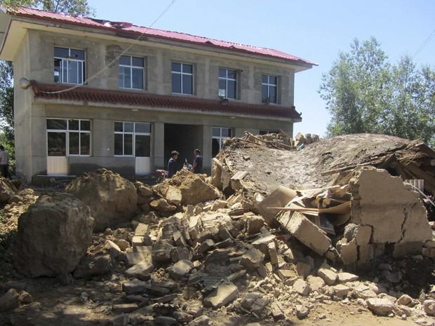 Moradores em frente a casa derrubada pelo terremoto no condado de Dingxi, na província chinesa de Gansu (Foto: Reuters)