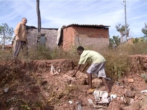 Morador escala barranco para ter acesso à própria casa (Foto: Reprodução/TV Anhanguera)