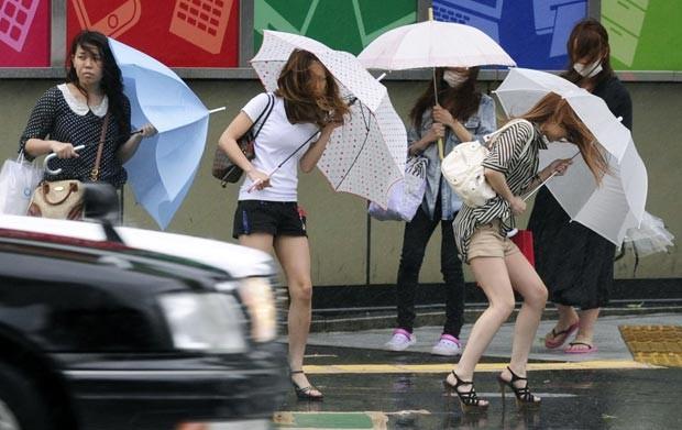 Mulheres tentam se defender dos ventos fortes nesta terça-feira (19) na cidade japonesa de Nagoya, antes da chegada do tufão Guchol (Foto: AP)