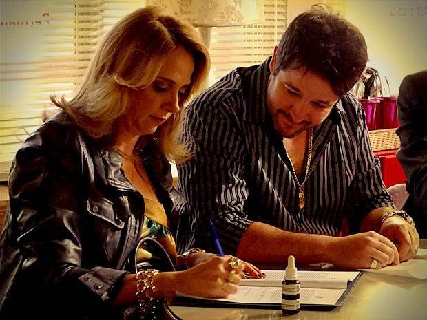 Ivana assina o contrato mesmo não querendo (Foto: Avenida Brasil / TV Globo)