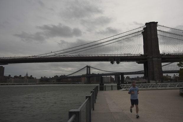 Morador de Nova York corre próximo à Ponte do Brooklyn neste domingo (28), com céu coberto de nuvens (Foto: Reuters)