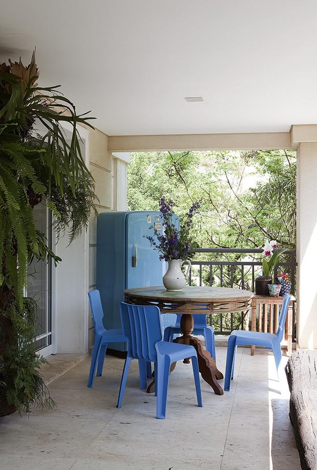 A velha geladeira azul, disposta na varanda, serve para guardar livros. A mesa foi trabalhada pela artista plástica Dedéia Meirelles, dona do apartamento, e as cadeiras Authentics, também azuis, são do designer Matthew Hilton (Foto: Marcos Antonio/Casa e Jardim)
