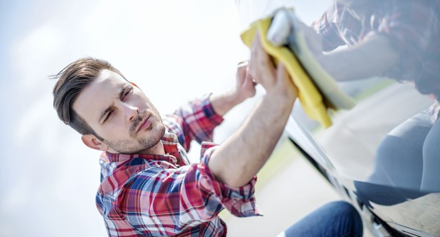 Young man cleaning his car outdoors.Man with a microfiber wipe the car polishing (Foto: Getty Images/iStockphoto)